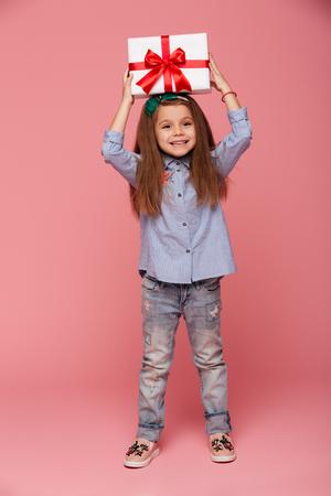 彼女の頭の上に赤いリボン弓を持つ喜びの女性の子供のフルレングスの肖像画は、ピンクの背景の上に喜びを感じています