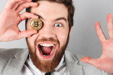 Close up of a happy businessman dressed in suit holding bitcoin at his face isolated over gray background
