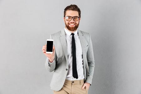 자신감 사업가의 초상화 서 회색 배경 위에 고립 된 카메라를 찾고있는 동안 빈 화면 휴대 전화를 보여주는 양복과 안경을 입고 스톡 콘텐츠 - 95134128