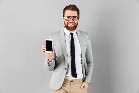 Portrait of a confident businessman dressed in suit and eyeglasses showing blank screen mobile phone while standing and looking at camera isolated over gray background