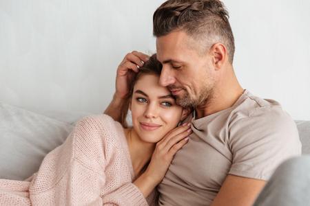 自宅で一緒にソファの上で休んで抱き合う若い愛情のあるカップルの肖像画