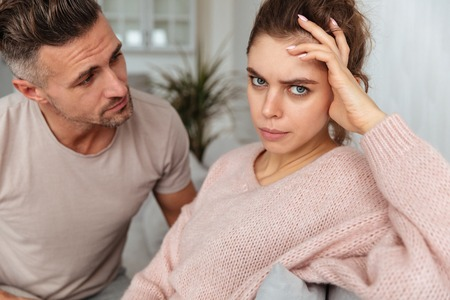 Close up image of attentive man sitting on couch and calm down his carefree girlfriend at home