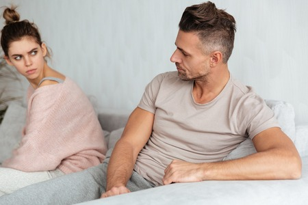 Image of Quarrelled lovely couple sitting separately on couch while looking to each other at home