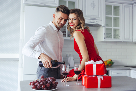 Happy woman with bright make up smiling to camera while her handsome man pouring wine into glasses at home on celebration 版權商用圖片