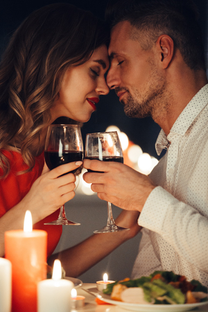 Young flirting beautiful lady in red dress kiss her gorgeous man while have romantic dinner at home