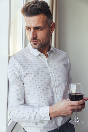 Portrait of a handsome pensive man dressed in shirt holding glass of wine while standing and looking at the window indoors Stock Photo