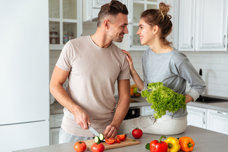 Portrait of a cheerful loving couple cooking salad together while standing on a kitchen at home, man cutting vegetables