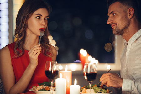 Young beautiful woman in red dress eating and flirting with her man while have romantic dinner in the evening