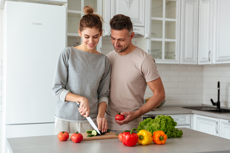 Portrait of a smiling loving couple cooking salad together while standing on a kitchen at home, woman cutting vegetables