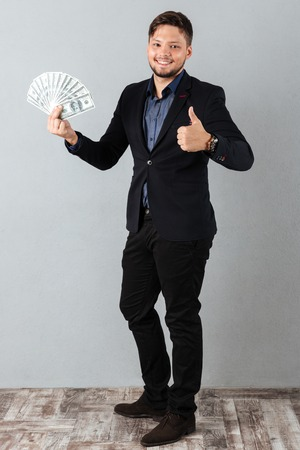 Full length portrait of a confident businessman holding bunch of money banknotes and showing thumbs up gesture isolated over gray background