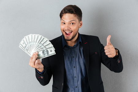 Portrait of a happy businessman holding bunch of money banknotes and showing thumbs up gesture isolated over gray background