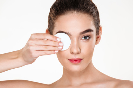 Close up photo of brunette beautiful woman removing her eye makeup with lotion and cotton pad, isolated over white background
