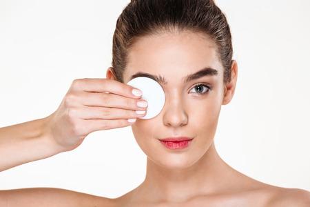 Schließen Sie herauf das Foto der Brunetteschönheit ihr Augenmake-up mit der Lotion und Baumwollauflage entfernend, lokalisiert über weißem Hintergrund