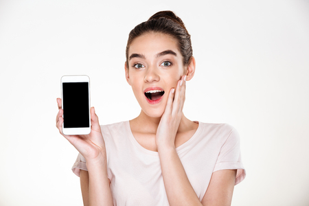Portrait of successful brunette female 30s rejoicing her new modern smartphone, showing it on camera over white wall