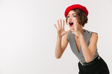 Portrait of an excited woman wearing red beret screaming loud isolated over white background