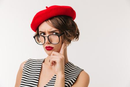 Retrato de una mujer decepcionada con boina roja y anteojos mirando a la cámara aislada sobre fondo blanco.
