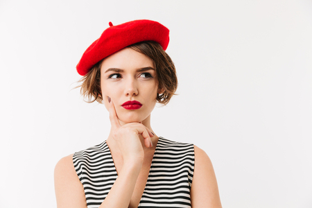 Portrait of a pensive woman dressed in red beret looking away isolated over white background 版權商用圖片
