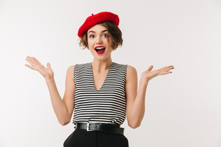 Portrait of a joyful woman dressed in red beret screaming and looking at camera isolated over white background