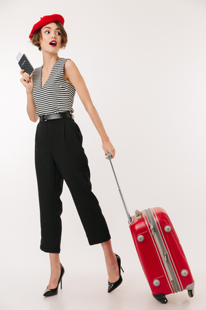 Full length portrait of a pretty woman wearing red beret walking with a suitcase while holding passport and looking away isolated over white background
