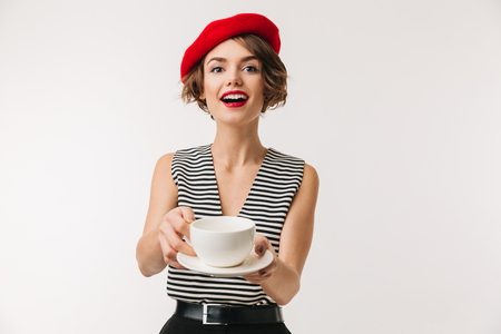 Portrait of n excited woman wearing red beret drinking tea from cup on a plate isolated over white background