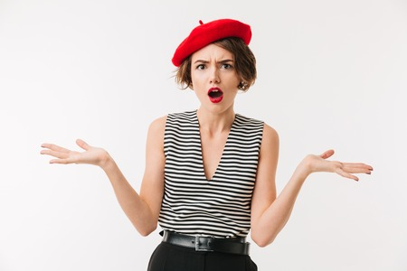 Portrait of a puzzled woman wearing red beret shrugging shoulders isolated over white background Stock Photo