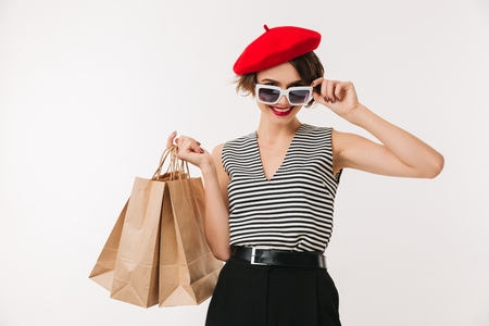 Portrait of a smilng woman wearing red beret and sunglasses holding shopping bags isolated over white background