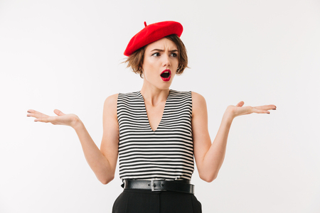 Portrait of a confused woman wearing red beret shrugging shoulders isolated over white background Stock Photo
