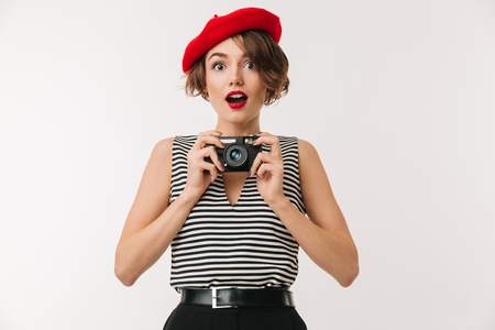 Portrait of a joyful woman wearing red beret holding photo camera and looking at camera isolated over white background