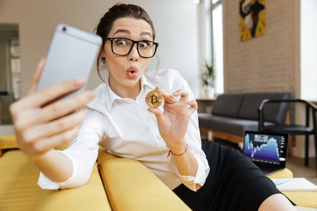 Photo of young excited emotional business lady talking by mobile phone sitting indoors coworking make selfie showing her golden bitcoin. Looking aside. Stock fotó