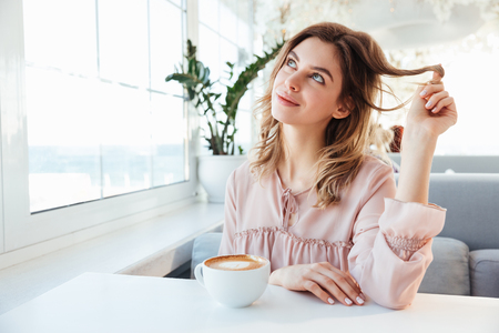 Portrait of dreaming young woman 20s resting in cozy city cafe, with cup of hot cappuccino on table
