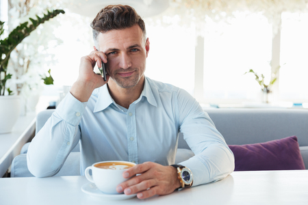 Portrait of handsome elegant man having mobile conversation when sitting alone in cafe with cup of caffeine beverage and looking on camera