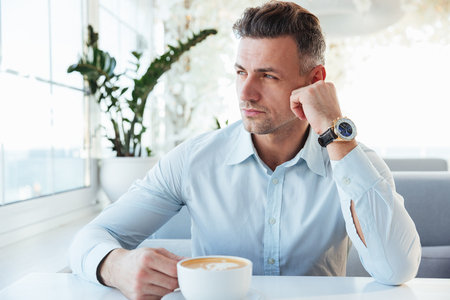 Photo of adult confident man 30s sitting alone in city cafe with cup of cappuccino and looking aside in window with meaningful sight