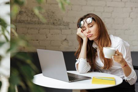 Portret zmęczonej młodej bizneswoman siedzi przy stole z laptopem, trzymając filiżankę kawy i spanie w kawiarni