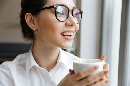 Image of young cheerful business woman sitting indoors drinking coffee looking at window.