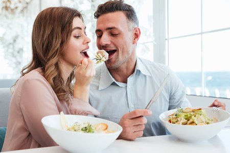 Portrait of happy romantic couple having dinner and eating salat together while having lunch break in restaurant