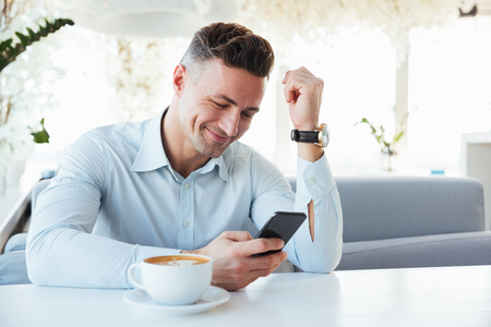 Image of happy elegant man sitting alone in city cafe with cup of cappuccino and typing text message using black mobile phone