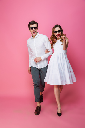 Full-length photo of fashionable married couple in sunglasses walking together on camera isolated over pink background