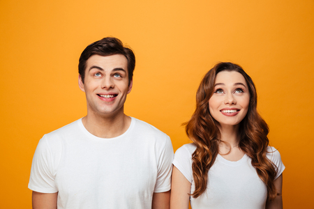 Photo of happy boyfriend and girlfriend in white t-shirts smiling and looking upwards isolated over yellow background
