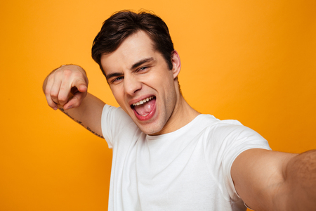 Playful man in t-shirt making selfie while pointing and looking at the camera over yellow background