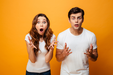 Portrait of a shocked young couple looking at camera isolated over yellow background