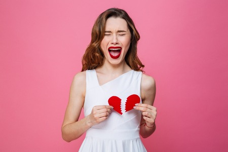 Photo of young screaming woman standing isolated over pink background holding broken heart. Фото со стока