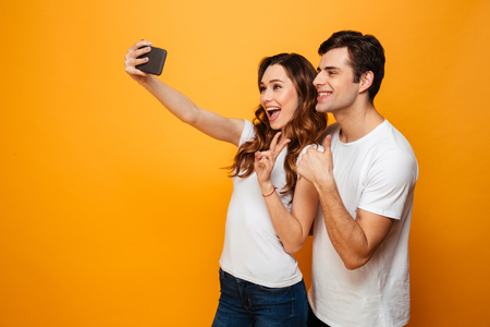 Pleased young lovely couple posing together while making selfie on smartphone and showing gestures over yellow background Stock Photo
