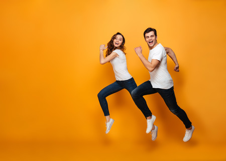 Young lovely cheerful couple posing together on camera while running or jumping along yellow background