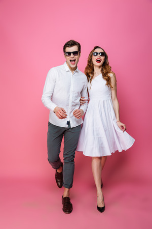 Full-length photo of modern fascinating lady and guy trendy dressed walking together on camera olated over pink background Stock fotó