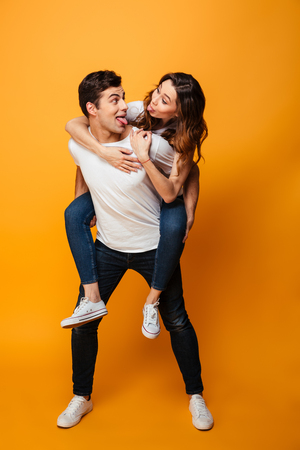 Full length image of Happy young lovely couple having fun while showing their tongues and looking to each other over yellow background
