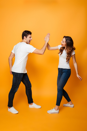 Full length image of happy young couple gaving five to each other over yellow background