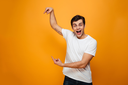 Surprised happy man in t-shirt pointing on copyspace and looking at the camera with open mouth over yellow background Stock Photo
