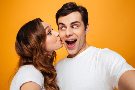 Display of affection of adorable couple girlfrined kissing her man in cheek over yellow background Imagens