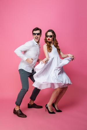 Full-length portrait of young energetic man and woman in classy stylish clothing dancing on camera isolated over pink background