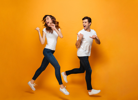 Photo of energetic beautiful couple running together along yellow backgroundand, and pointing fingers backward on copyspace
